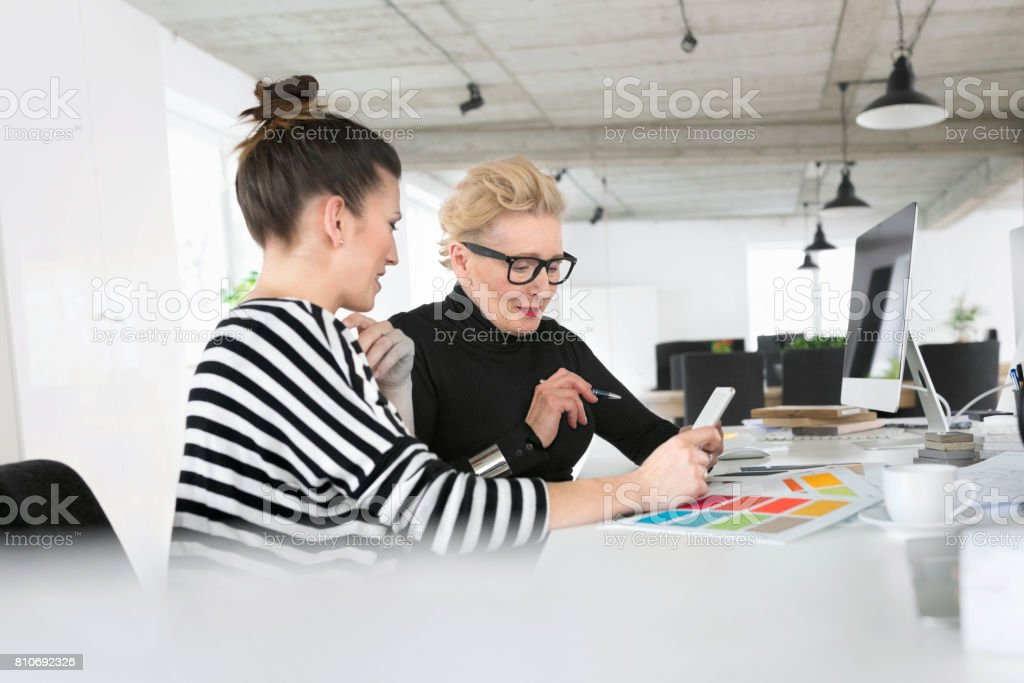 Senior and young interior designers using a digital tablet in the studio Senior interior designer working together with young woman in the office, sitting at the desk and using a digital tablet together. 60-69 Years Stock Photo