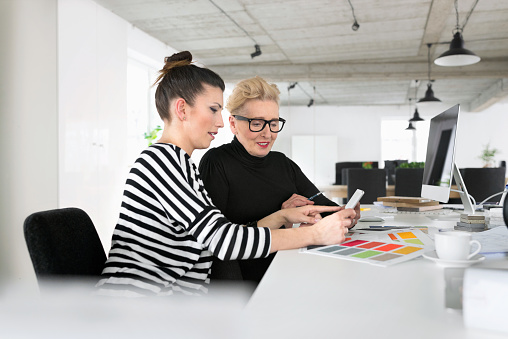 Senior And Young Interior Designers Using A Digital Tablet In The Office Stock Photo - Download Image Now