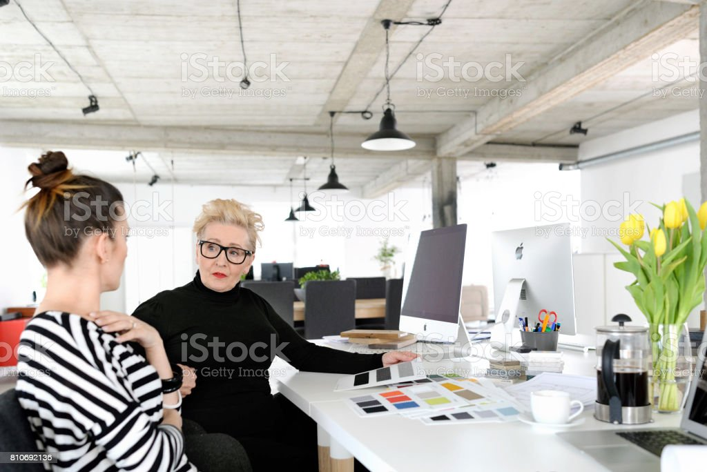 Senior and young interior designers working together with young woman in the studio Senior interior designer working together with young woman in the office, sitting at the desks and discussing a project. 60-69 Years Stock Photo