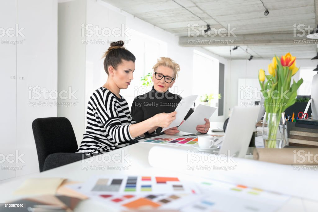 Senior and young interior designers working together with young woman in the office Senior interior designer working together with young woman in the office, looking at documents. 60-69 Years Stock Photo