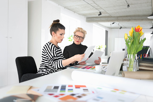 Senior And Young Interior Designers Working Together With Young Woman In The Office Stock Photo - Download Image Now