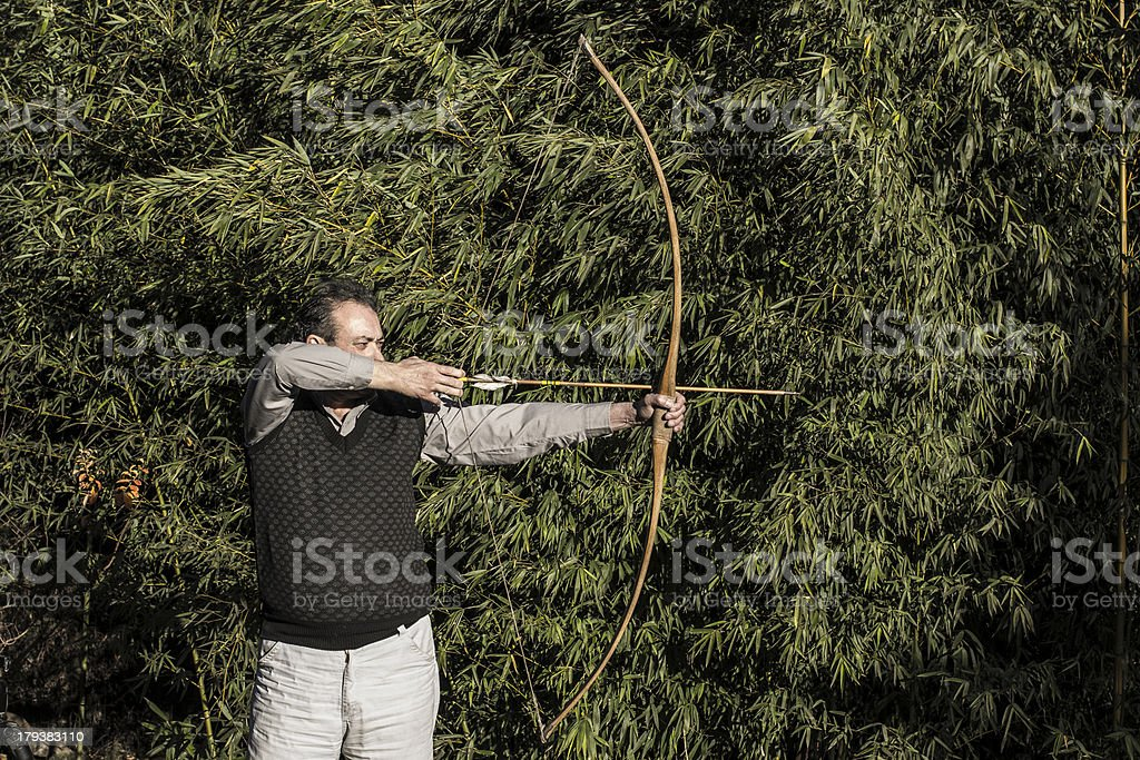Senior Archer with Selfmade Arrow and Bow in Garden royalty-free stock photo