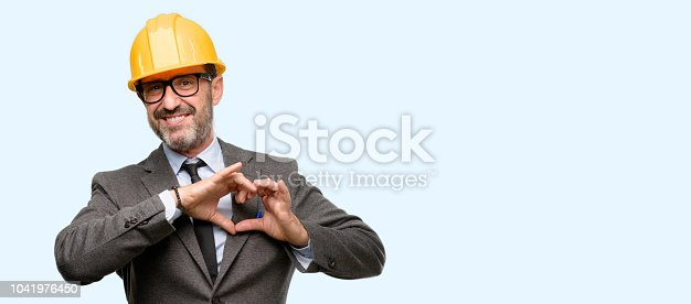 istock Senior architect or engineer happy showing love with hands in heart shape expressing healthy and marriage symbol 1041976450