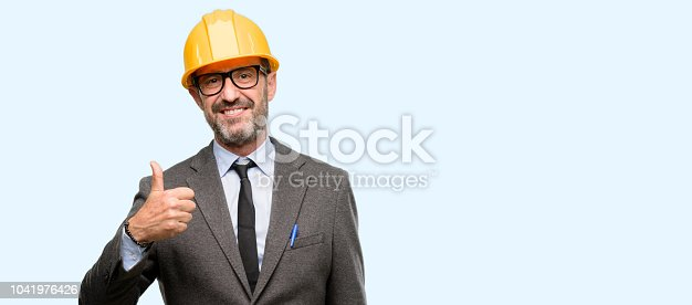 istock Senior architect or engineer smiling broadly showing thumbs up gesture to camera, expression of like and approval 1041976426