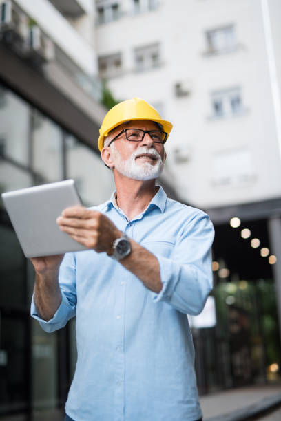 Senior architect using digital tablet. stock photo