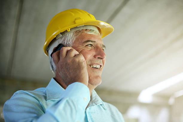 Senior architect using smart phone. stock photo