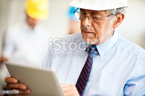 istock Senior Architect with colleagues in background 528072726
