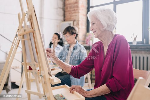 Side view portrait of art students sitting in row and painting at easels in art studio, focus on smiling  senior woman enjoying work copy space