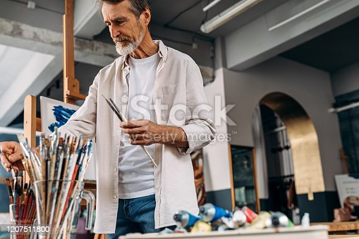 Senior artist standing in studio picking paintbrush for drawing