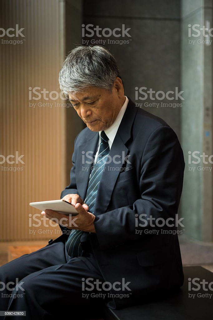 Senior Asian business executive with tablet royalty-free stock photo