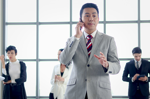 Senior Asian businessman boss in suit talking on mobile phone at the window office workplace with business people colleague as blurred background.