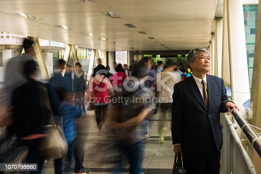 Senior Asian businessman standing out from the crowd