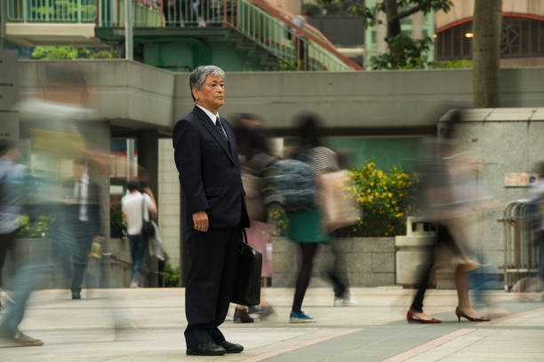 Senior Asian businessman standing out from the crowd stock photo