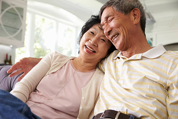 Senior Asian Couple At Home Relaxing On Sofa Together stock photo