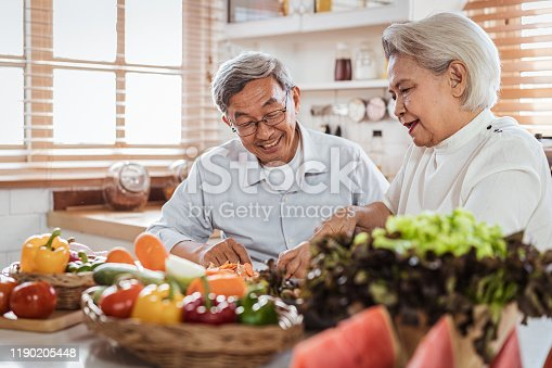Senior Asian couple love cooking together in the kitchen with happiness