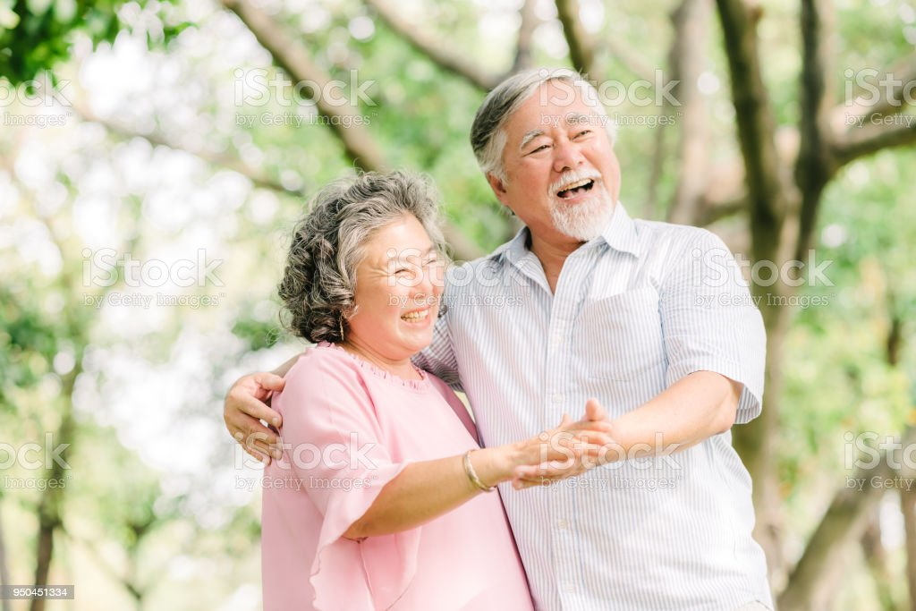 senior Asian couple dancing in the park stock photo