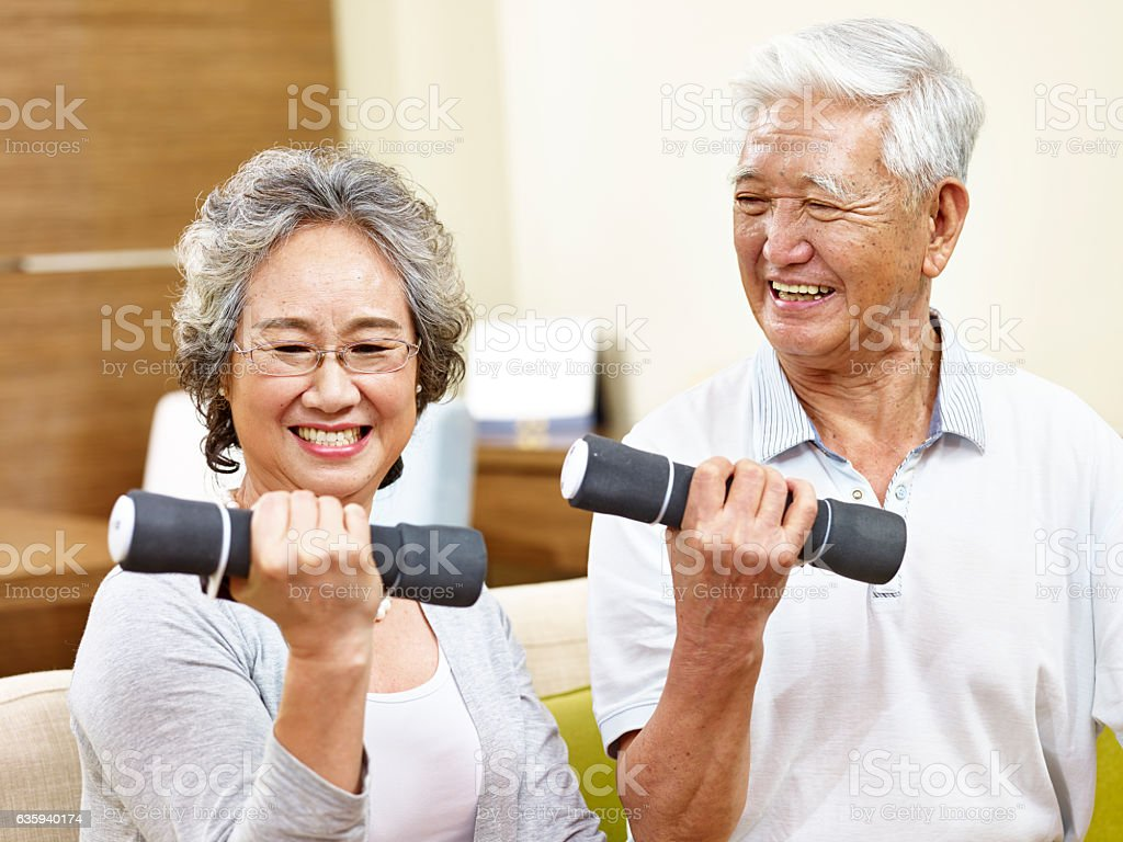 senior asian couple exercising using dumbbells stock photo