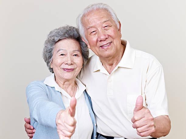 Senior Asian couple giving thumbs-up stock photo