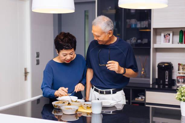 Hochrangige asiatische paar Großeltern zusammen zu kochen, während Frau Mann in der Küche Essen eingezogen wird. Lang anhaltende Beziehung Konzept – Foto