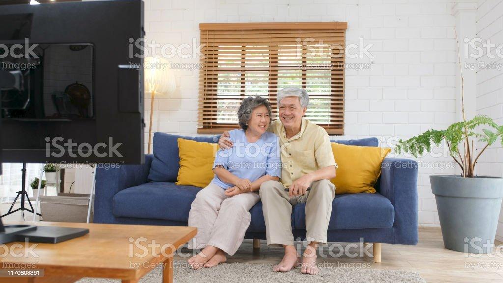 Senior asiatische paar hält Fernbedienung beim Fernsehen im heimischen Wohnzimmer mit Glück, alte Menschen Ruhestand Routine Lebensstil - Lizenzfrei 60-69 Jahre Stock-Foto