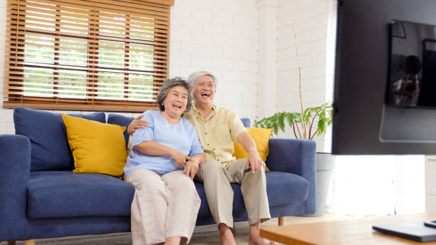 Senior asian couple holding remote control while watching television in home living room with happiness, old people retirement routine lifestyle stock photo