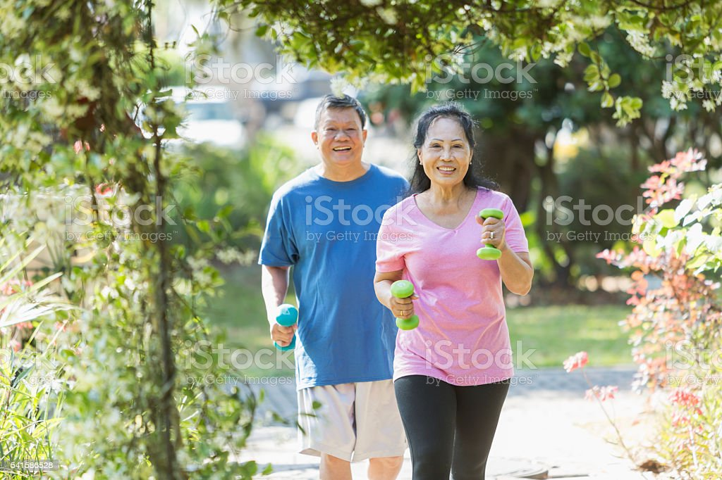 Senior Asian couple in park exercising together stock photo