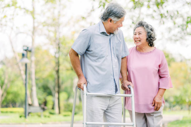 senior Asian couple laughing while walking with walker stock photo