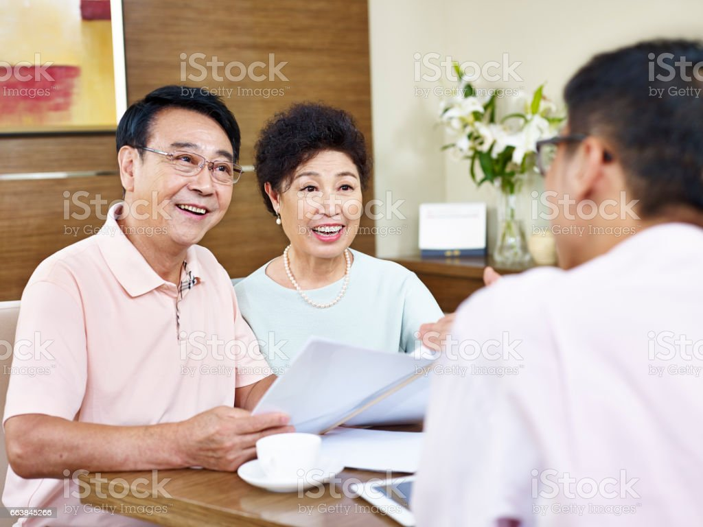 senior asian couple listening to a sales agent stock photo