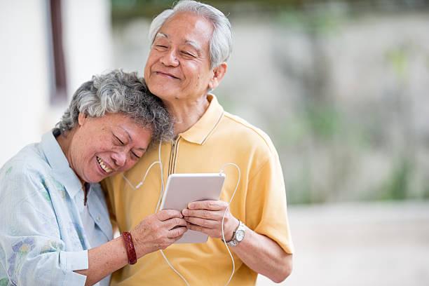 Senior Asian Couple Listening to Music stock photo
