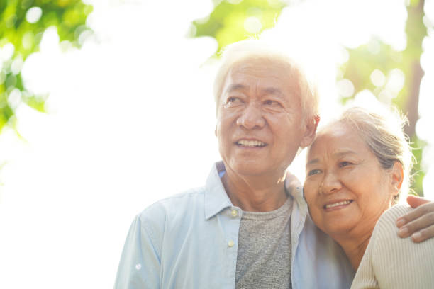 senior asian couple relaxing outdoors stock photo