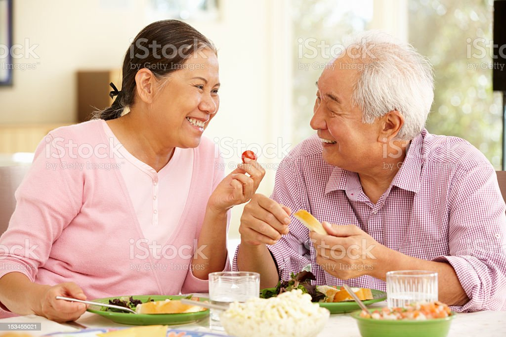 Senior asian couple sharing meal at home stock photo