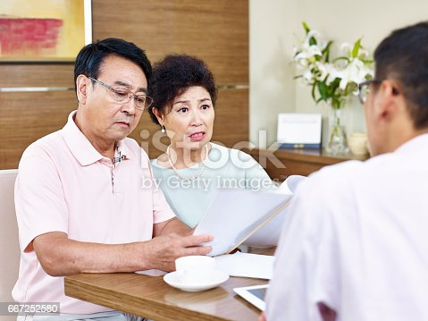 istock senior asian couple shocked while reading a contract 667252580