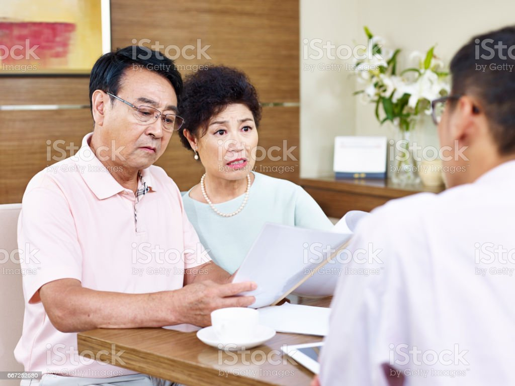 senior asian couple shocked while reading a contract stock photo