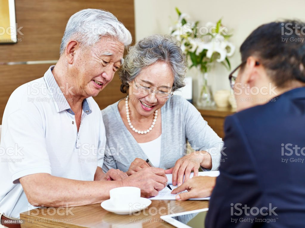 senior asian couple signing a contract stock photo