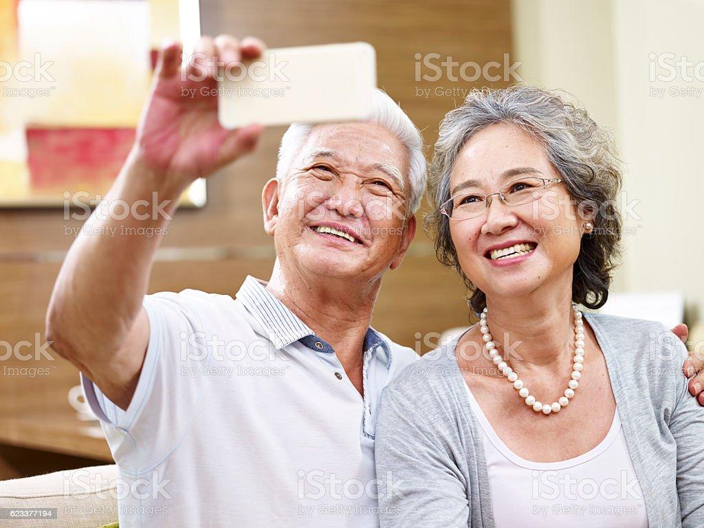senior asian couple taking a selfie stock photo