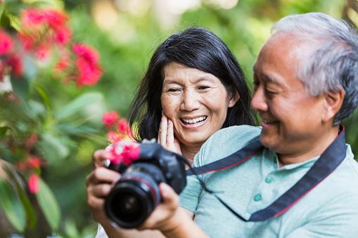 Senior Asian couple taking photographs with camera