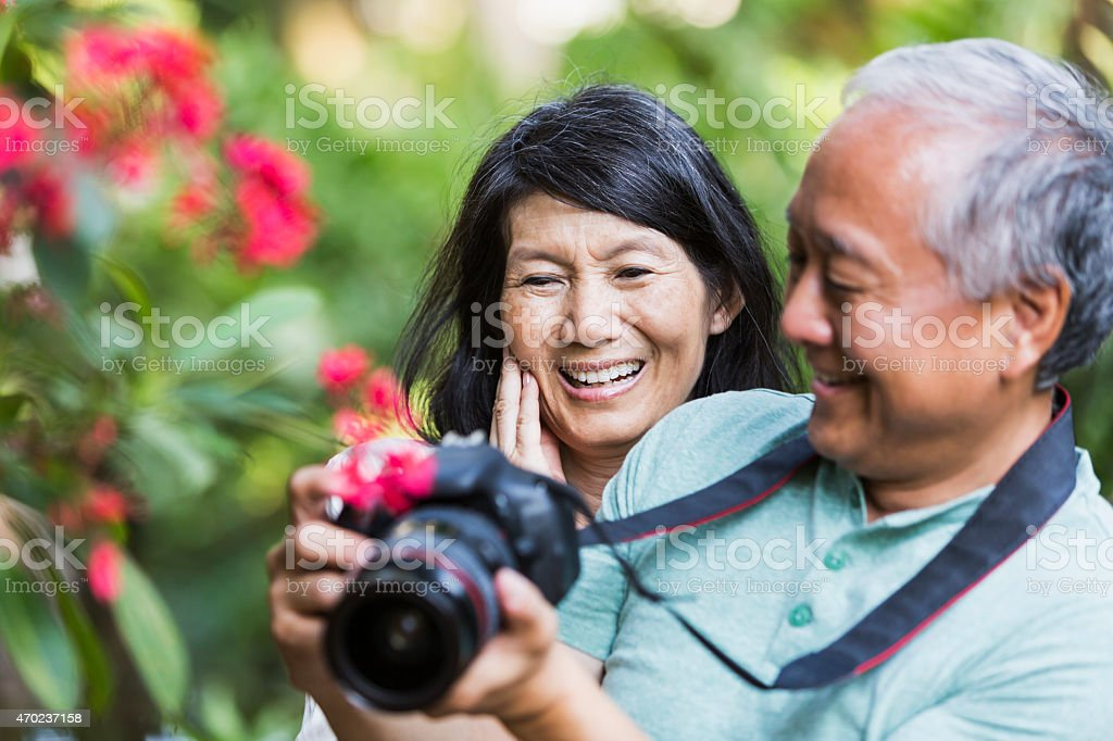 Senior Asian couple taking photographs with camera stock photo