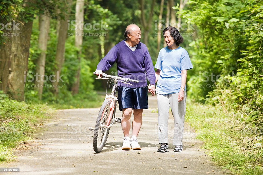 A senior Asian couple walking on a trail with a bicycle royalty-free stock photo