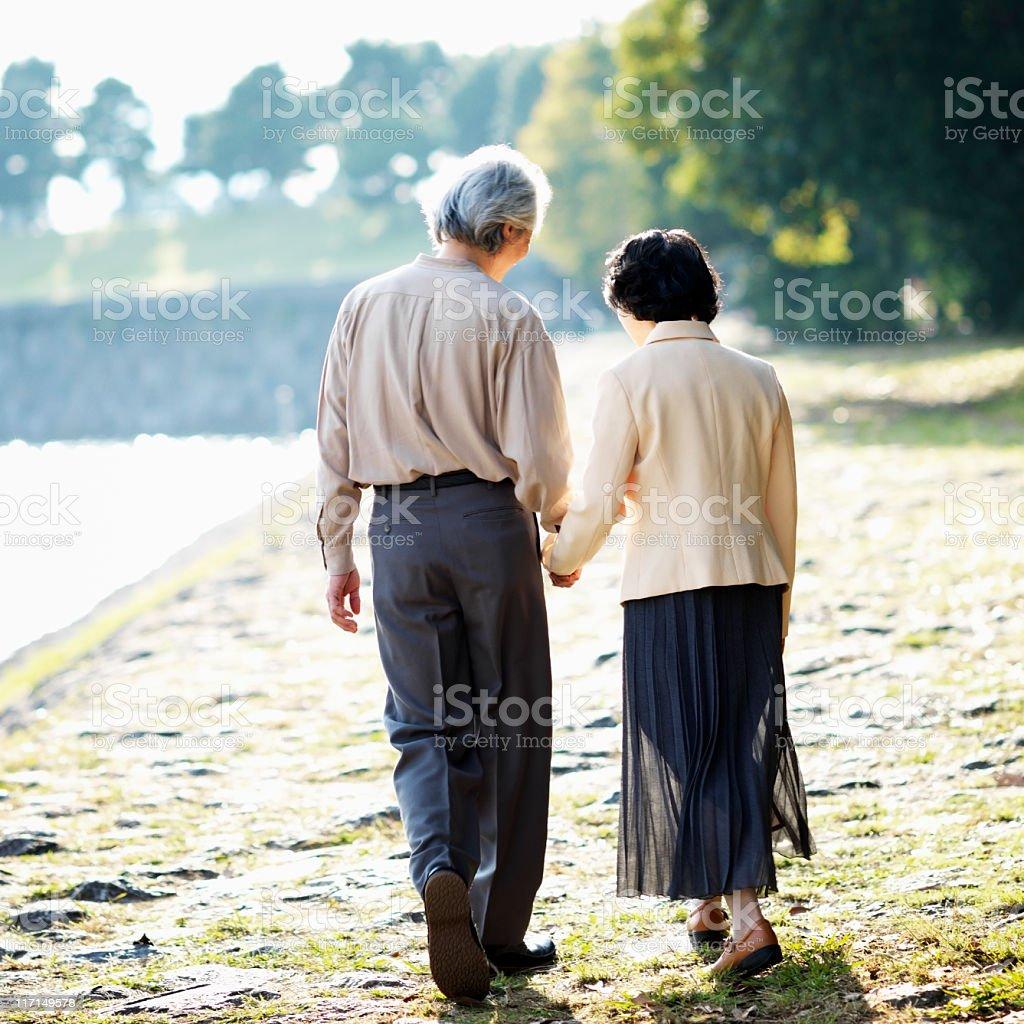 Senior Asian Couple Walking on the Lake Shore royalty-free stock photo