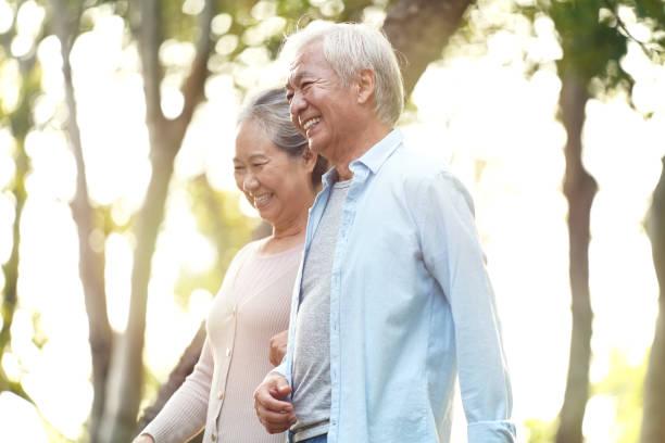 senior asian couple walking outdoors in park stock photo