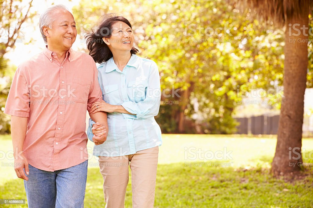 Senior Asian Couple Walking Through Park Together stock photo