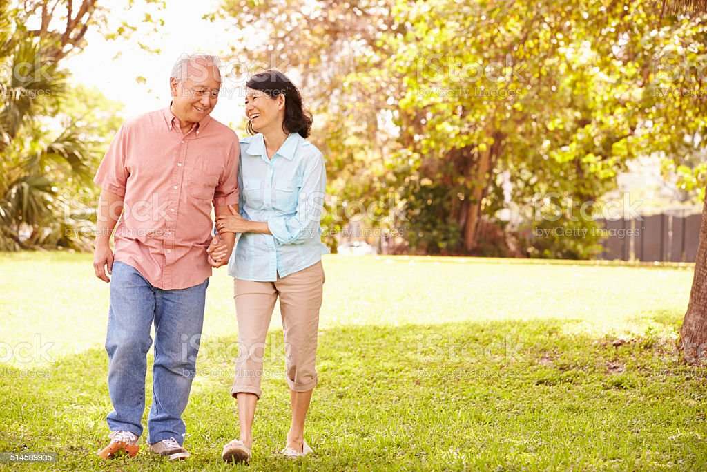 Senior Asian Couple Walking Through Park Together stock photo