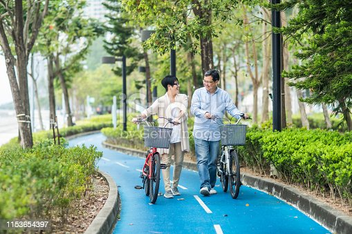 istock Senior asian couple with bicycles in the park. 1153654397