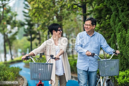 istock Senior asian couple with bicycles in the park. 1153654529