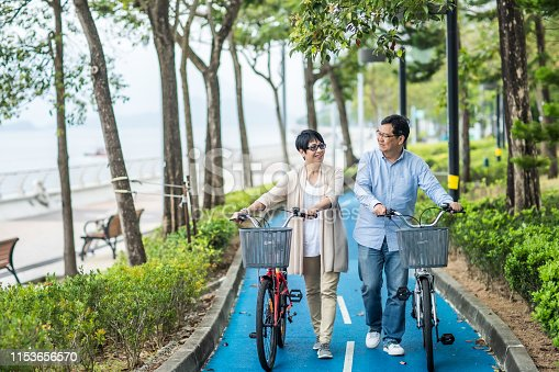istock Senior asian couple with bicycles in the park. 1153656570