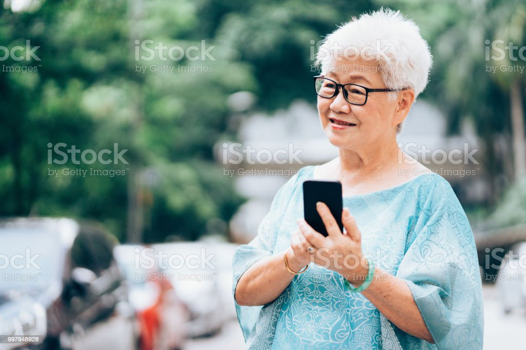 Senior Asian ethnicity woman in the city using smart phone