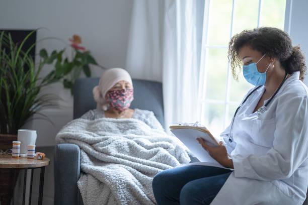 senior asiatische krebspatientin trägt maske im gespräch mit arzt - chemotherapie stock-fotos und bilder