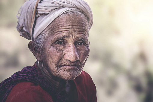 Old Indian/Asian woman with wrinkles elderly senior,  sitting outside her village home.
