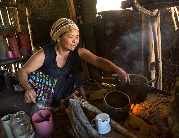 Senior Asian lady cooking with wood fire An old Asian lady is cooking with wood fire in her hut, Flores island in Indonesia. indonesian ethnicity stock pictures, royalty-free photos & images