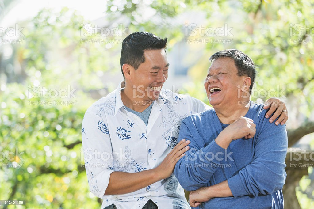 Senior Asian man and adult son laughing together stock photo
